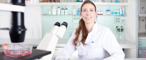 trenzyme's scientific expert for stable cell line development with microscope and titer plate