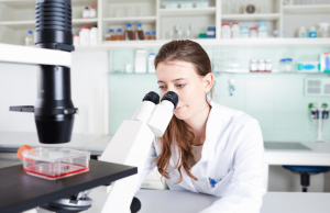 trenzyme's scientific expert with microscope and titer plate